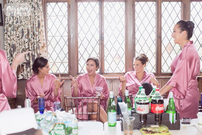 The bridesmaids have a good laugh while getting ready for the wedding at the Crane Estate Tavern.