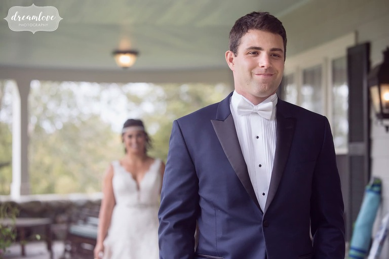 The groom has the sweetest smile on his face before the first look on the porch at the Crane Estate Inn.