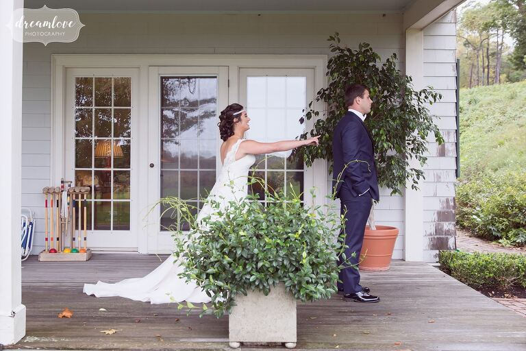 The bride taps the groom on the shoulder for their first look at the Crane Estate Inn.
