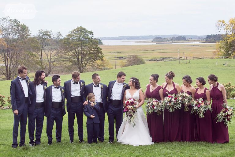 Wedding party stands on the front lawn of the Castle Hill Inn with the salt marsh behind them.
