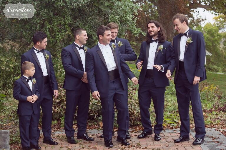 Candid moment of the groomsmen trying to figure out how to lift up the groom.