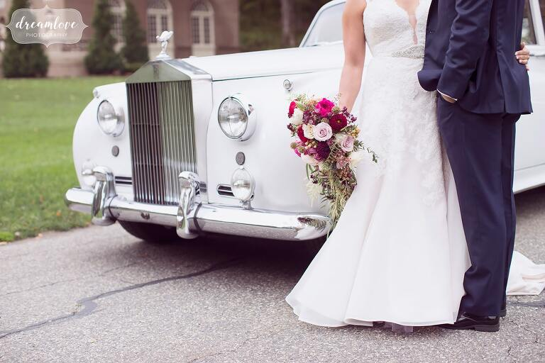 The bride and groom lean against their Rolls Royce at the Crane Estate.