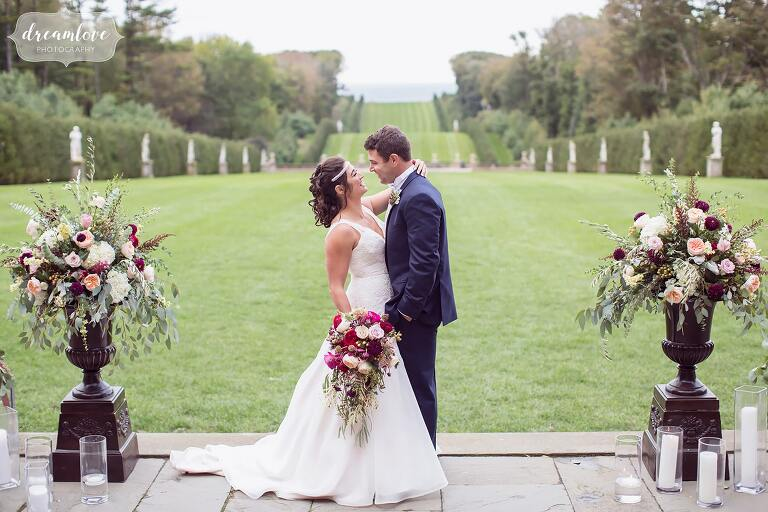The bride and groom kiss in front of the rolling hills lawn at this storybook wedding venue on the northshore of Boston.