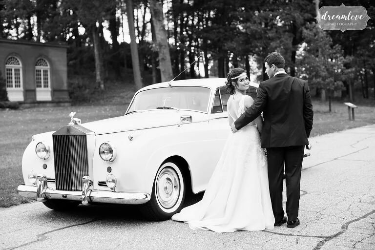The bride looks back at the camera in this black and white photo with their Rolls Royce at the Crane Estate.
