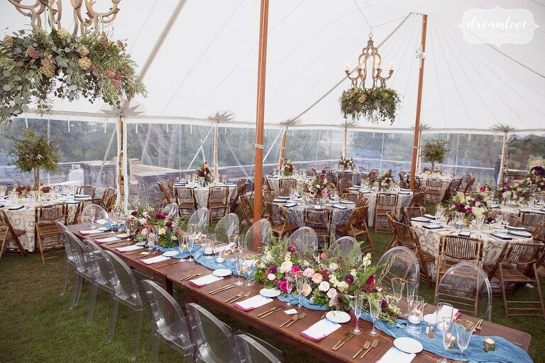 The tented reception space next to the Crane Estate castle is filled with family style wooden tables and tons of flowers.