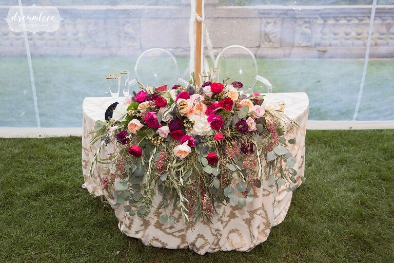 Tons of flowers cascade over the sweetheart table at this Crane Estate wedding in the tent.