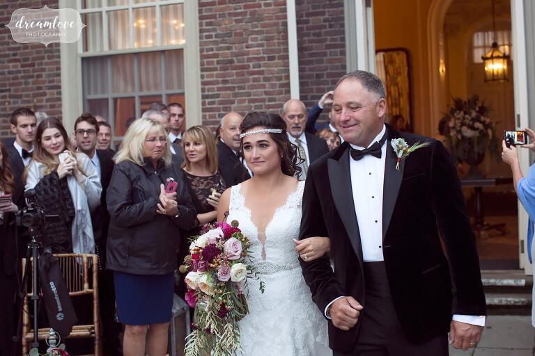 The bride walks in with her father at this Crane Estate terrace ceremony.