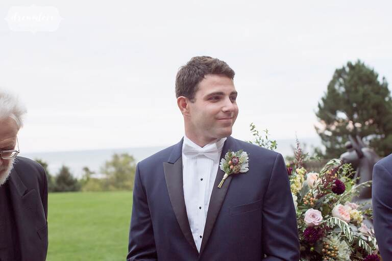 Natural wedding photography of the groom watching the bride enter ceremony.
