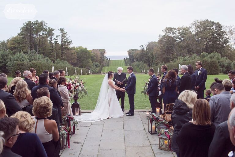 The bride and groom hold hands during this epic coastal wedding ceremony at the Crane Estate just north of Boston on the ocean.