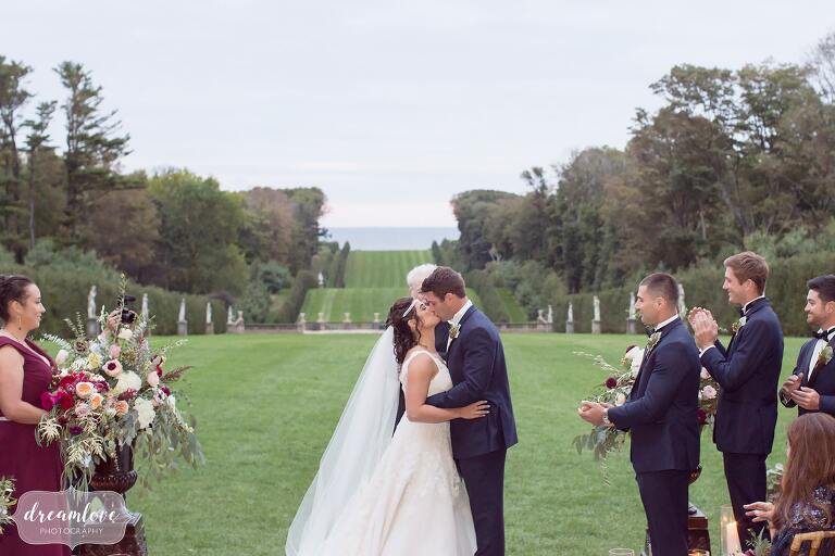 The bride and groom kiss at the end of the ceremony with the ocean behind them at this storybook wedding.