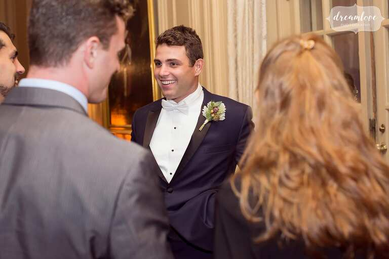Groom talking with wedding guests in the ballroom at the Crane Estate.