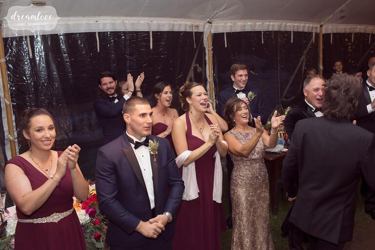 The wedding guests cheer and clap as the bride and groom enter the tented reception at the Crane Estate.