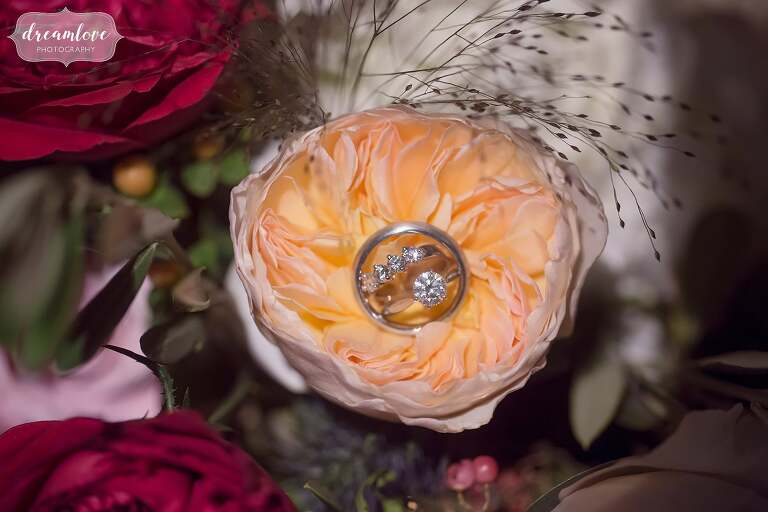 Storybook wedding detail of wedding rings inside of a large rose peony.