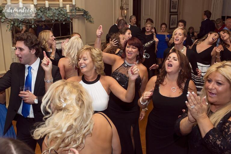 Storybook wedding guests dance in ballroom.