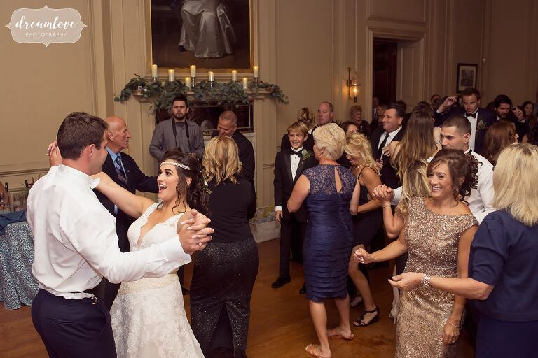 The bride and groom smile at each other on the dance floor at the Crane Estate.