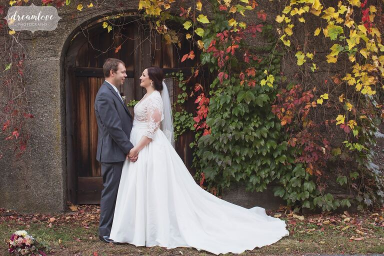 The bride and groom in front of an antique door at the Larz Anderson Auto Museum in Boston.