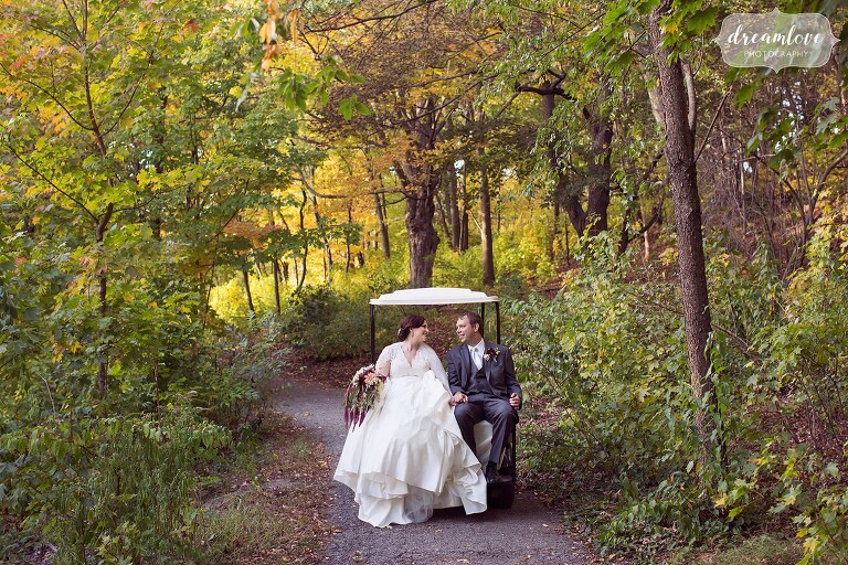 The bride and groom ride on the back of a golf cart through a tiny woodsy path at the Larz Anderson park.