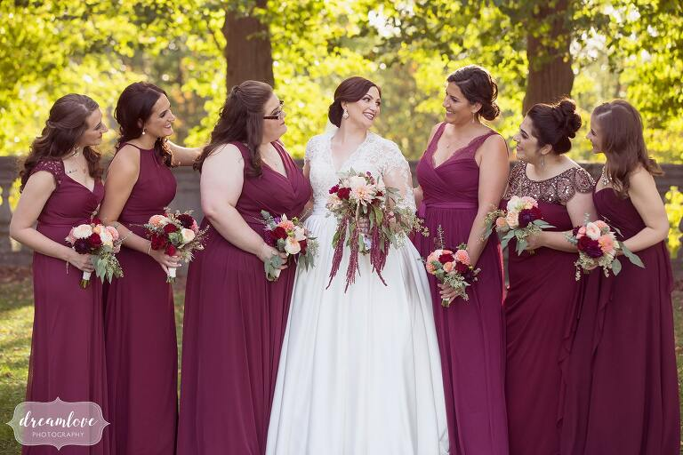 Bridesmaids all smile at the bride in maroon dresses for this fall wedding at the Larz Anderson Auto Museum.