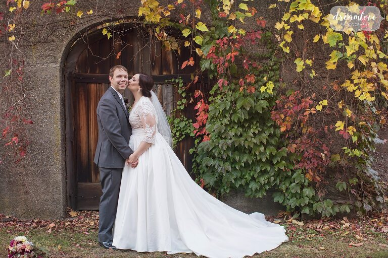 The bride kisses her groom on the cheek surrounded by fall foliage before their October outdoor wedding in Boston at the Larz Anderson Museum.