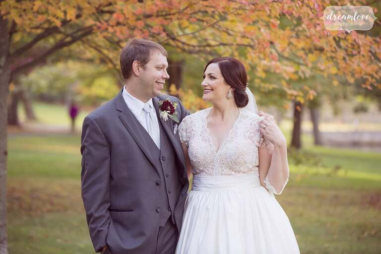 This bride and groom stand in front of beautiful fall color at the Larz Anderson Park in Boston.