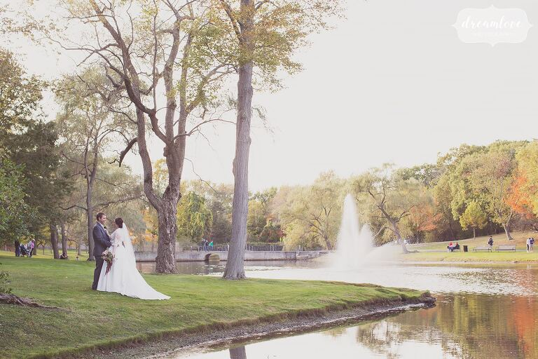 The bride and groom stand on the edge of the lake in Larz Anderson Park for their October wedding outside.