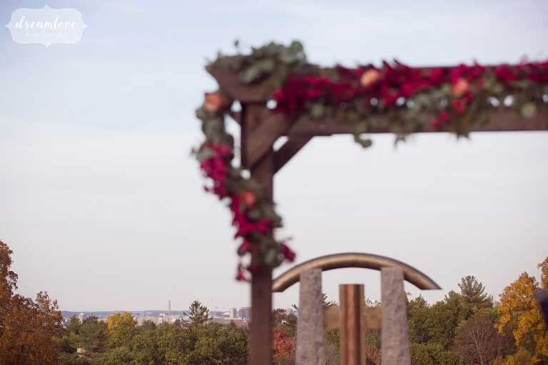 This rustic wooden ceremony arbor is draped in fall colors with the Boston skyline behind at this outdoor wedding venue called Larz Anderson.