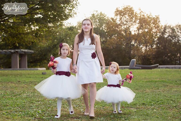 Trio of flower girls with maroon sashes walk down the aisle at this Boston wedding venue.