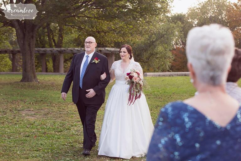 The bride and her dad walk down the aisle at outdoor Boston wedding.