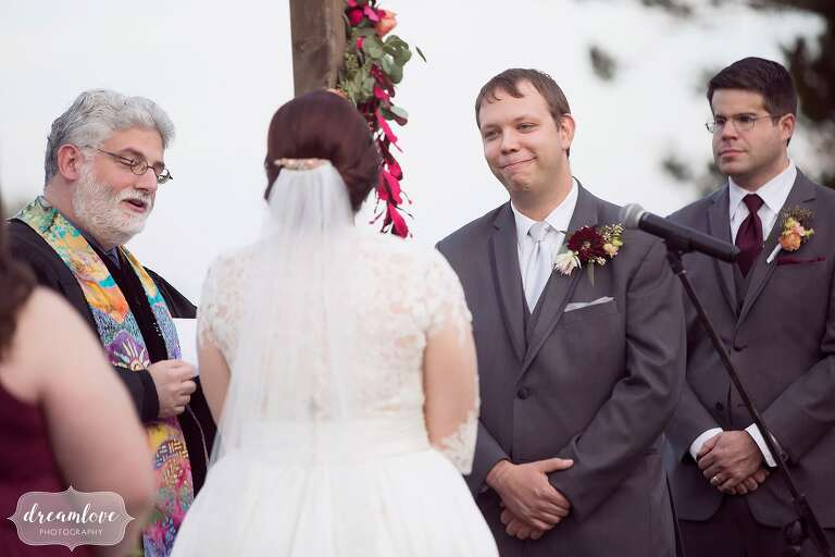 The groom smiles at the bride during their outdoor wedding ceremony on the hilltop at Larz Anderson Park.