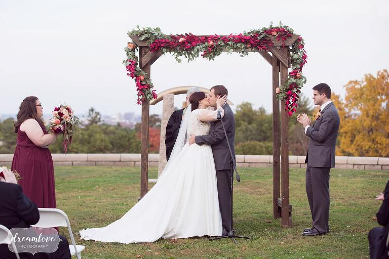The bride and groom kiss under a rustic wooden arbor draped in maroon flowers at the Larz Anderson hilltop.