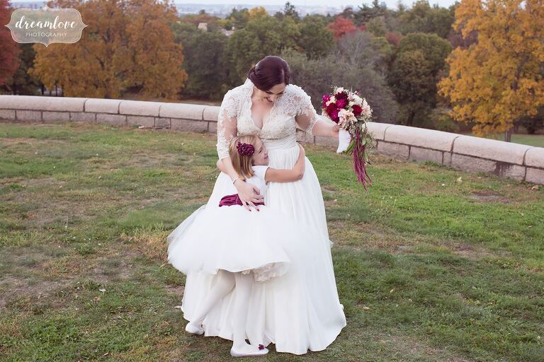 Candid wedding photo of the flower girl hugging the bride at Larz Anderson Auto Museum.