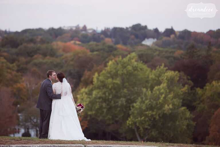 The bride and groom kiss on the hilltop with October fall foliage behind them at the Larz Anderson Park venue in Boston.