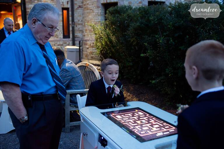 Little boy super entertained by playing an old arcade game in a modern table design at Larz Anderson Boston wedding.
