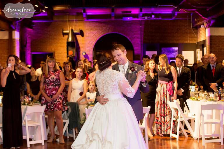 The bride and groom have their first dance among pink uplighting at Larz Anderson.