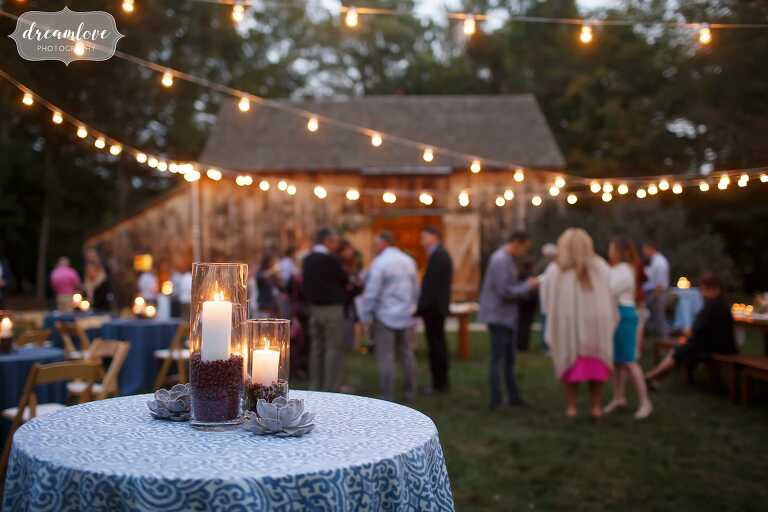 Cafe lights are strung up over tables at this outdoor rehearsal dinner at the Gould Barn.
