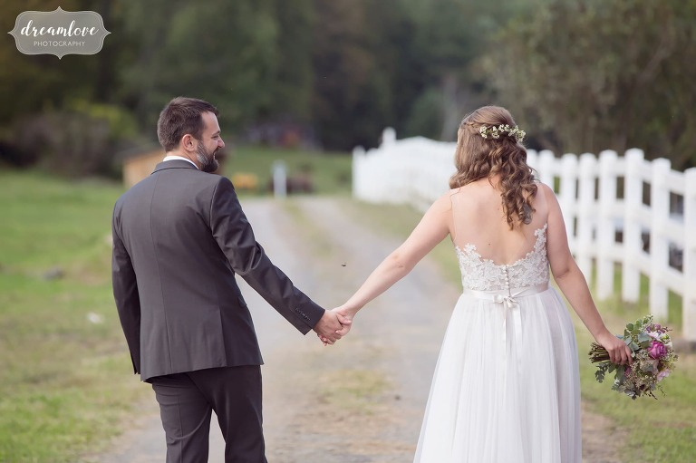 Western MA wedding photographers capture bride and groom holding hands and walking away at Berkshire East.