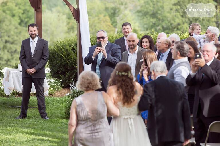 Bride walks with her parents down the aisle at the Warfield House Inn.