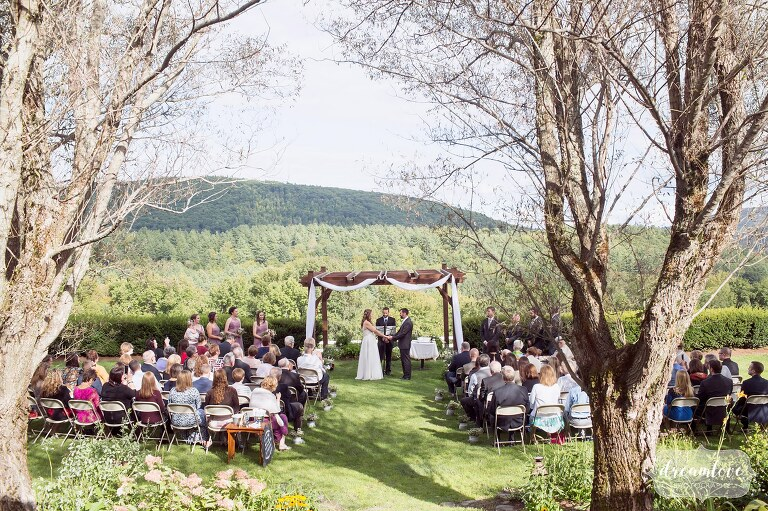 View of the outdoor ceremony space surrounded by mountains at the Warfield House Inn in Charlemont, MA.
