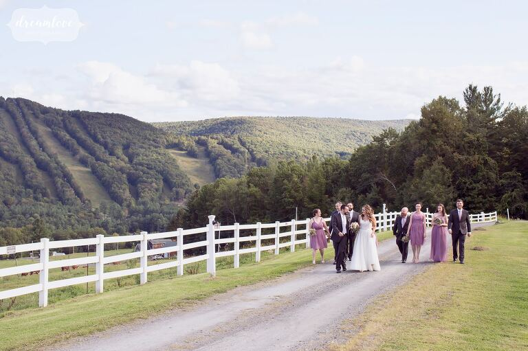 The wedding party walks along the white fence with the Berkshire East Ski Resort in the background.