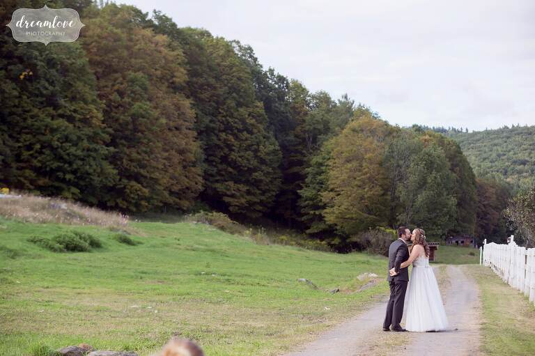 Romantic wedding photo of the bride and groom kissing on gravel path at the Warfield House Inn.