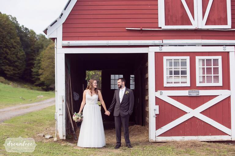 The bride and groom stand in the doorway of a red barn at the Warfield House Inn venue in western MA.