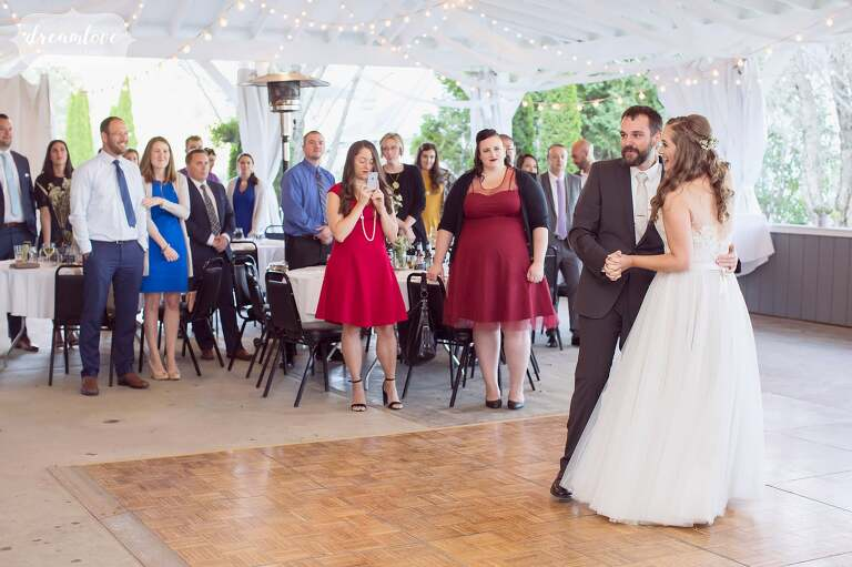 The bride and groom have their first dance in this white barn at the Warfield Inn.