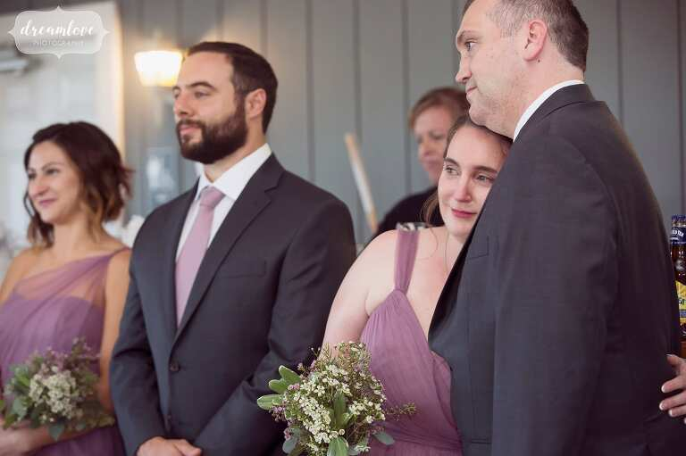 Candid wedding photo of the bridesmaid crying while watching the first dance at the Warfield House Inn reception.
