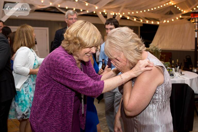Candid wedding photo of the mother of the bride hugging her old friend at Berkshire East wedding.