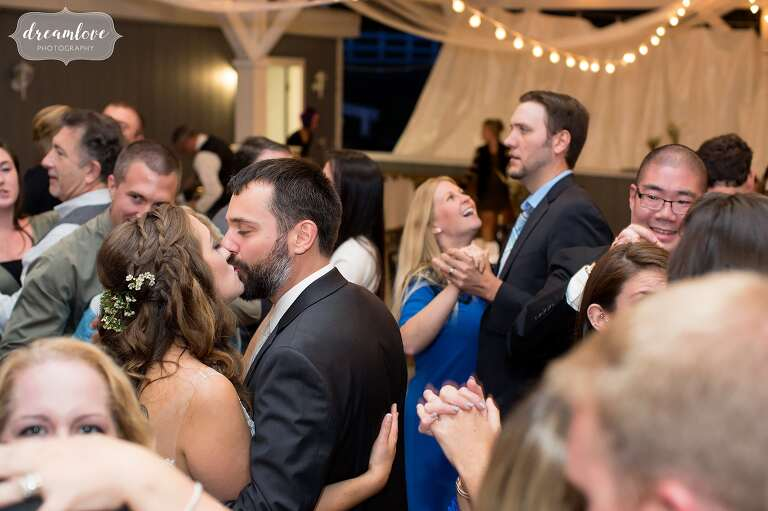The bride and groom kiss on the dance floor at this Warfield House Inn wedding.