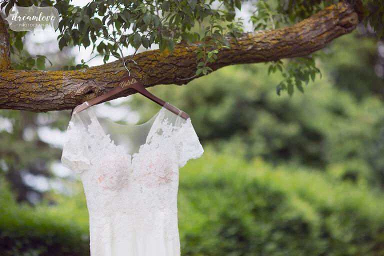 The bride's dress hangs in the woods at this seaside camp wedding in NY.