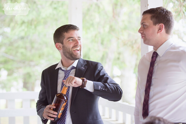 The groom gets ready to take a drink from the Old Granddad whiskey at this NY camp wedding.