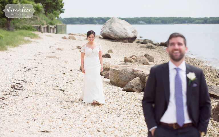 The bride and groom have their first look on the beach at this NY camp wedding.