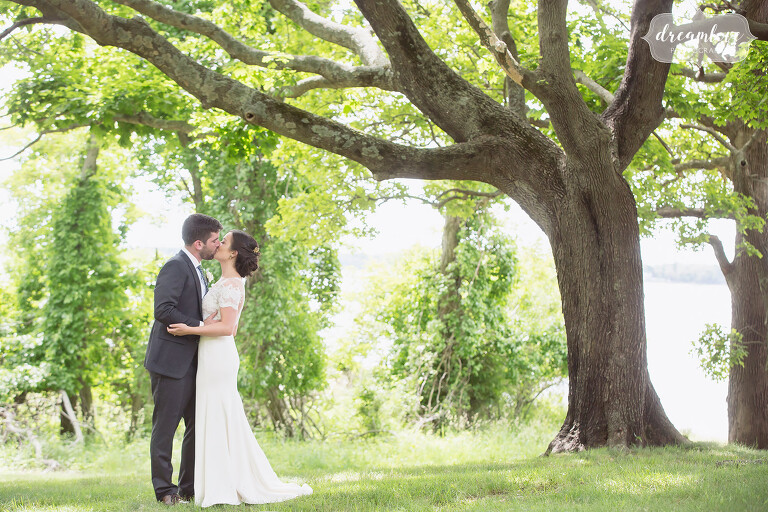A romantic photo of the bride and groom kissing under trees by the ocean at this NY camp wedding.