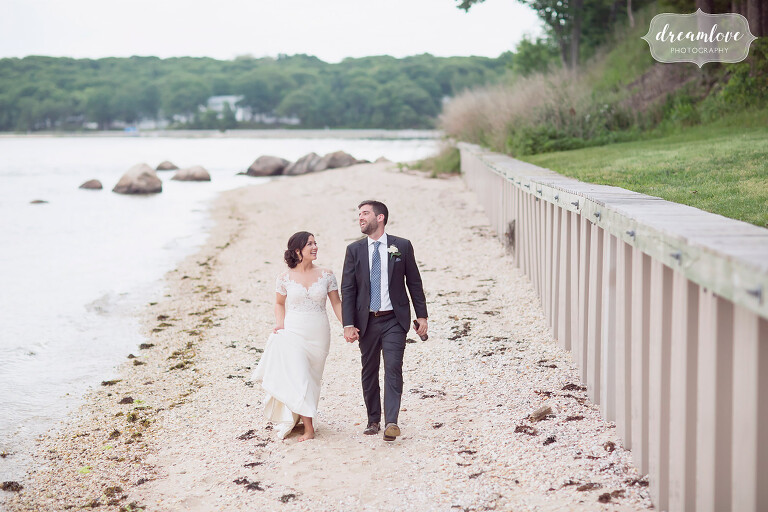 The bride and groom walk along the beach at their Shelter Island wedding in NY.